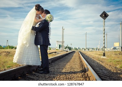 groom embraces the bride on rails. Happy young bride and groom on their wedding day. Wedding couple - new family! wedding dress. Bridal wedding bouquet of flowers