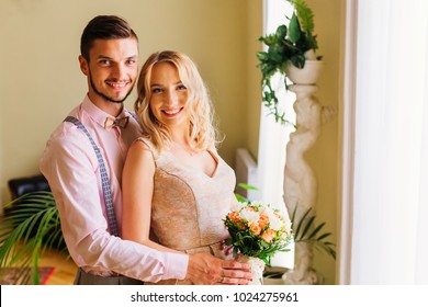 The groom embraces her bride who holds a wedding bouquet in a room with decorations
