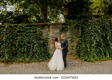 groom embracing bride on street in front of old wall with ivy