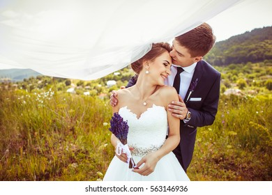 The groom embracing her bride