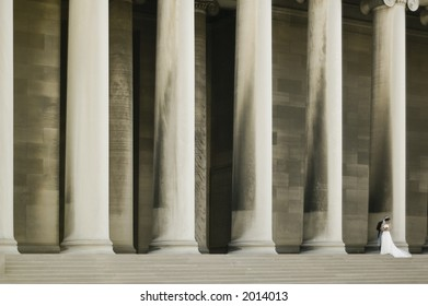 A groom embracing his bride in front of a row of enormous columns