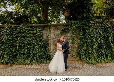 groom embrancing bride in front of old wall with ivy