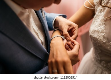 The groom fastens the bracelet on the bride's wrist. Cropped image