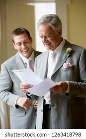 Groom and father of the bride rehearsing speech on wedding day