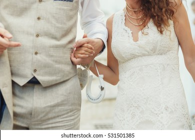 Groom in flexen suit holds bride's hand while they walk