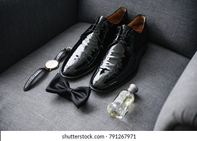 The groom is gathering in the morning. A gray chair.  Men's Black classic patent leather shoes. A black bow tie. Wedding details. Eau de toilette, perfume, watch with leather strap.