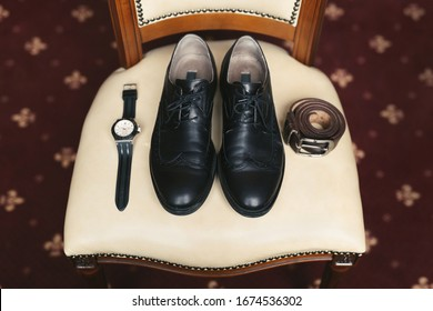 Groom is gathering in the morning.Men's  classic  shoes, belt,toilette, perfume, leather strap watch, wedding rings.