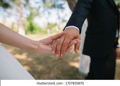 the groom gently holds the bride's hand on the wedding day on a beautiful background