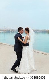 groom gently touched to the bride on a pier near the sea