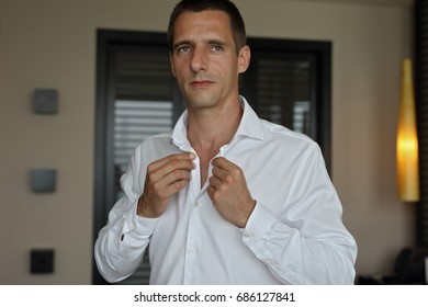 Groom getting ready for wedding. Elegant man bottoning white shirt , fashion portrait.