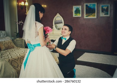 a groom is giving a wedding bouquet of pink flowers to his bride