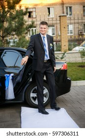 The groom goes out of the car on a white path for  a wedding ceremony