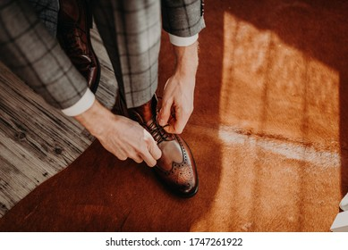 The groom in grey black checkered suit a white shirt, sitting on the couch and tied shoelaces on brown leather shoes. Shoes for business clothing, men's style.