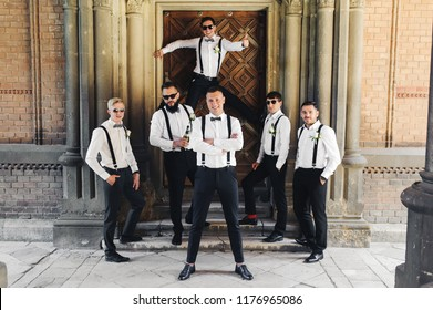 Groom and groomsmen in black trousers pose between columns