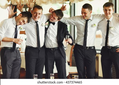 Groom and groomsmen have fun while posing in the restaurant
