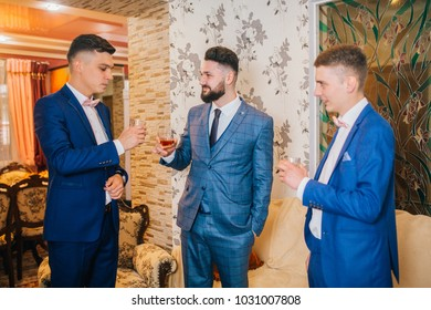 Groom and groomsmen look funny standing in the garden. Best friends on wedding day.
