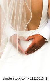 Groom heart hands around bride