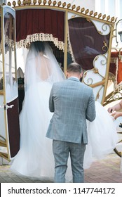 groom helping bride with dress to enter the fairy carriage