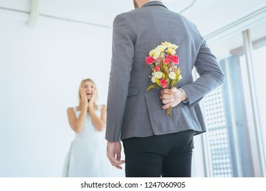 Groom hiding flower behind back in order to surprised  bride on the wedding day,Woman positive emotion and face astonished happy and smling