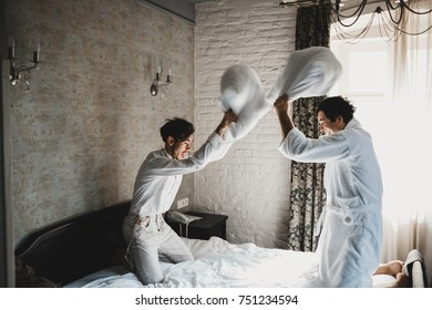 Groom and his groomsman fight with pillows on the bed