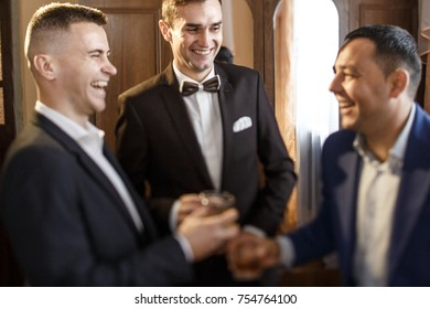 groom and his groomsmen friends in stylish suits drinking whiskey in hotel room, morning before the wedding preparation, emotional group of friends celebrating
