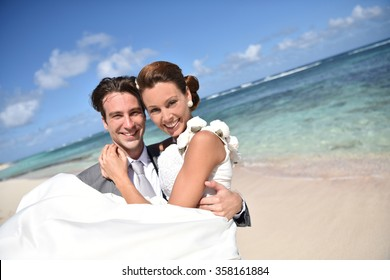 Groom holding bride in arms at the beach