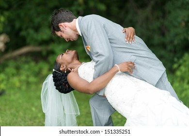 Groom holding bride in dance pose on wedding day