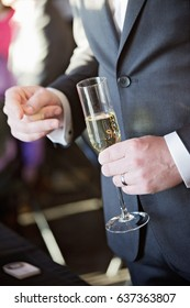 Groom holding champagne glass at reception
