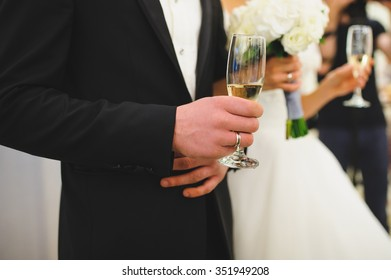 groom holding glass of champagne at ceremony