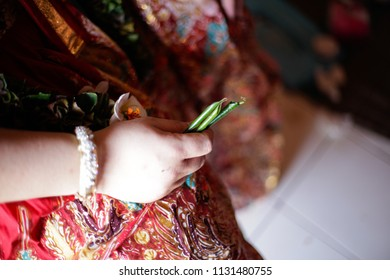 Groom is holding a green leaves on his hand for traditional Javanese wedding ceremony called lempar sirih