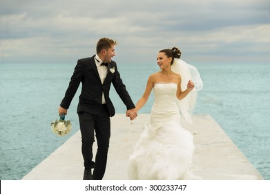 The groom is holding his bride by the hand. They are running on the pier.