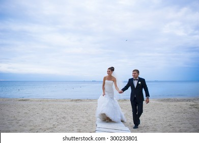 The groom is holding his bride by the hand. They are walking on the beach.