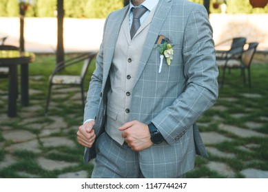 groom holding jacket at sunny cafe