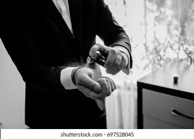 The groom is holding perfume. groom have a final preparation for wedding - man holing a parfume bottle and spraying fragrance on hand