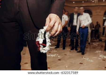 59954ac09 groom holding silk garter from bride at wedding party. tradition of  throwing bridal garter to