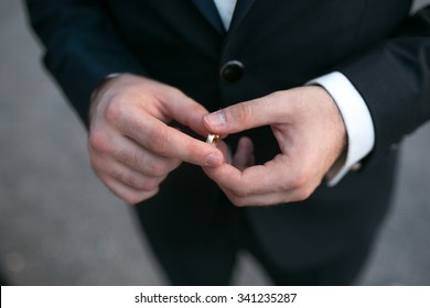 groom holding a wedding ring and waits for bride