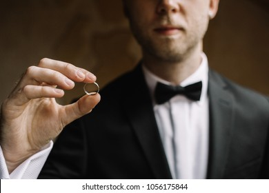 Groom holding wedding rings on the palm, the groom in a blue suit, groom holding wedding rings, groom's hand holding a ring, wedding ring in groom hand