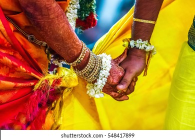 groom holds bride hand in south Indian traditional wedding ceremony