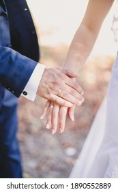 Groom holds bride hand in white dress. Blurred background. High quality photo