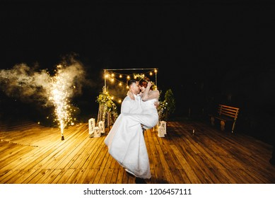 The groom holds the bride on the background of the wedding decor at nigh