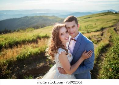 Groom holds bride tender standing before beautiful landscape