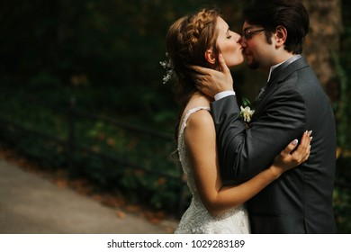 Groom holds bride's face tender while she kisses his nose somewhere in the park