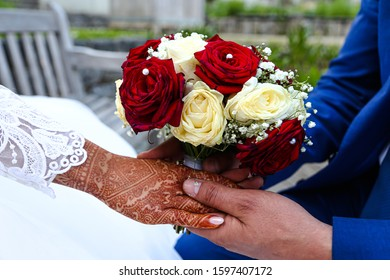 A groom holds the bride's hand. The bride's hand is decorated with henna tattoos. In the background a bouquet of flowers