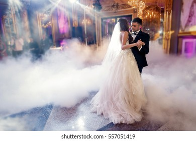 Groom holds bride's hands tender while they dance in the smoke