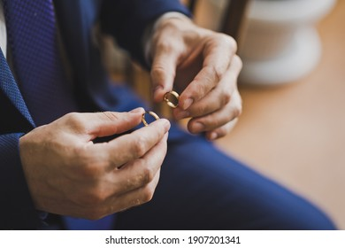 The groom holds the gold wedding rings with his fingers.
