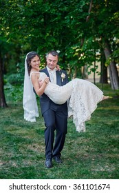 groom holds his bride in his arms and smiles of happiness.