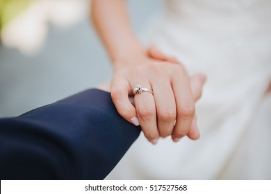 The groom holds his bride's hand. the bride's wedding ring on the finger
