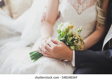 groom holds his bride's hand on a background of lake