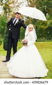 Groom holds an umbrella above a bride