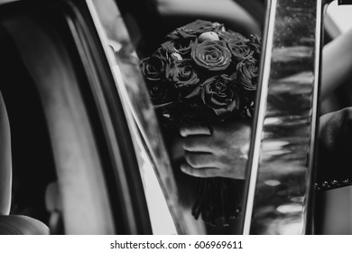 Groom holds wedding bouquet in his hands sitting in the car